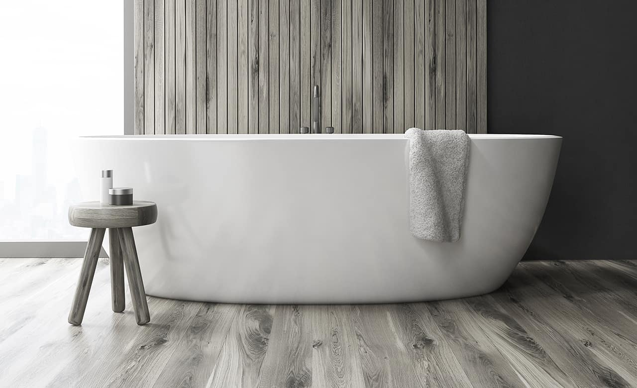 Bathroom with a tub and a wooden wall